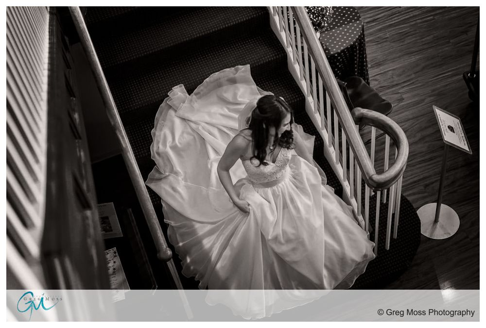 Bride walking down stairs holding wedding dress on her way to the first look