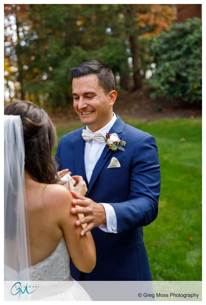 Groom in blue suit holding bride during first look