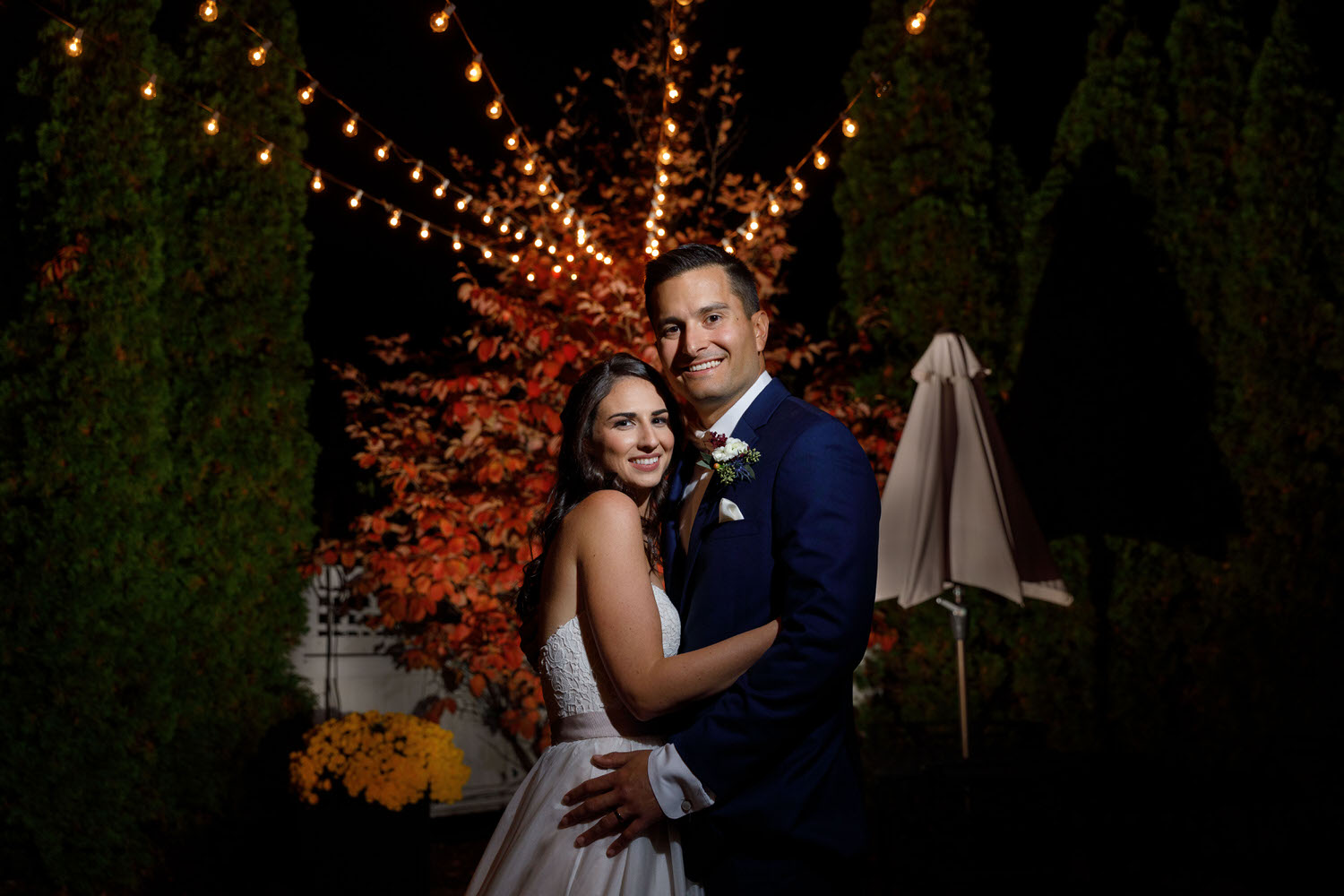 Bride and groom at night with string lights