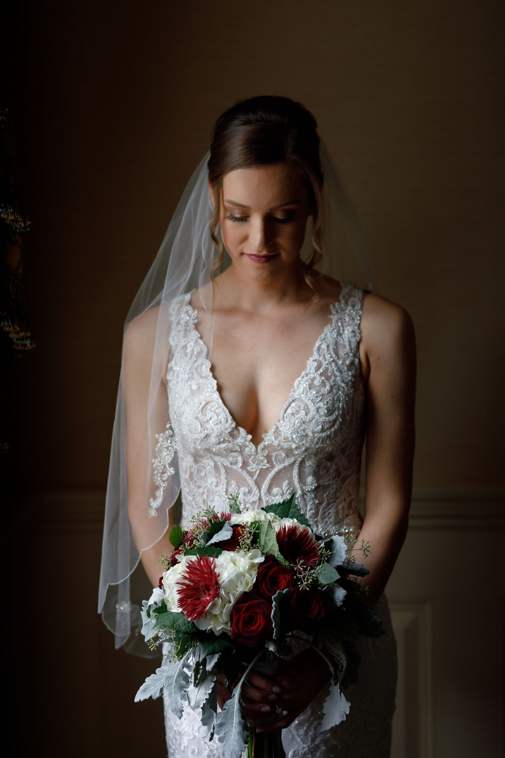 Beautiful Bride with window light holding wedding bouquet