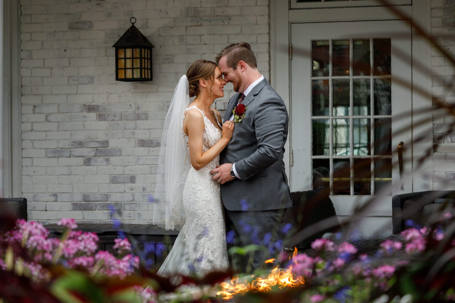 Bride and Groom embracing in front of the fire and flowers in front of the Inn on Boltwood