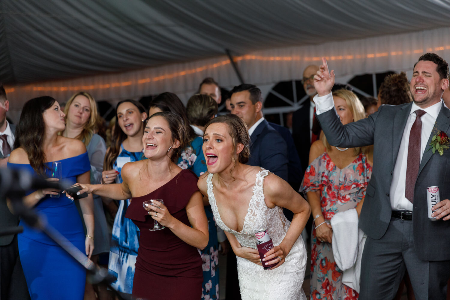 Bride and bridesmaid shouting for the band during wedding reception