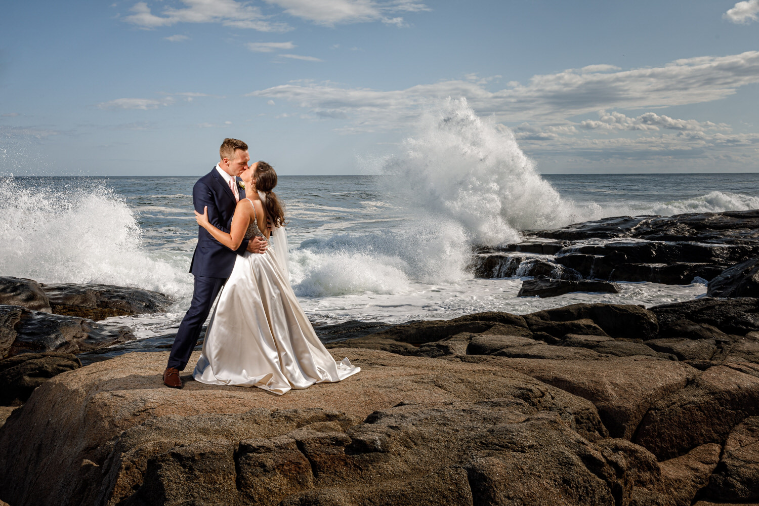 Bride and Groom on rock in front of Atlantic Ocean with big wave in the background