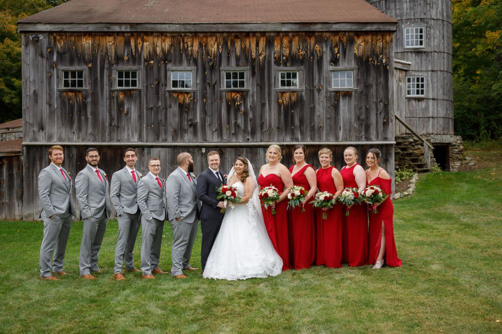 Full wedding party with rustic barn behind them