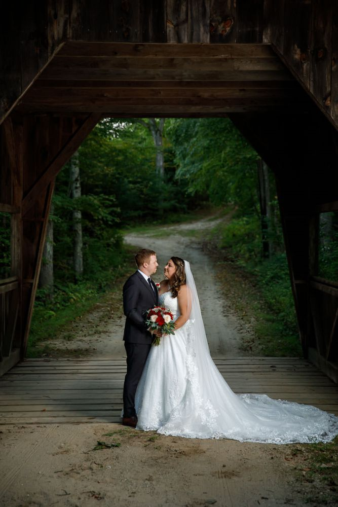 Bride and groom under covered bridge at Wrights Mill Farm