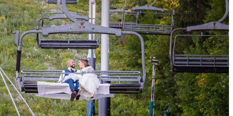 Bride and groom riding up chair lift.