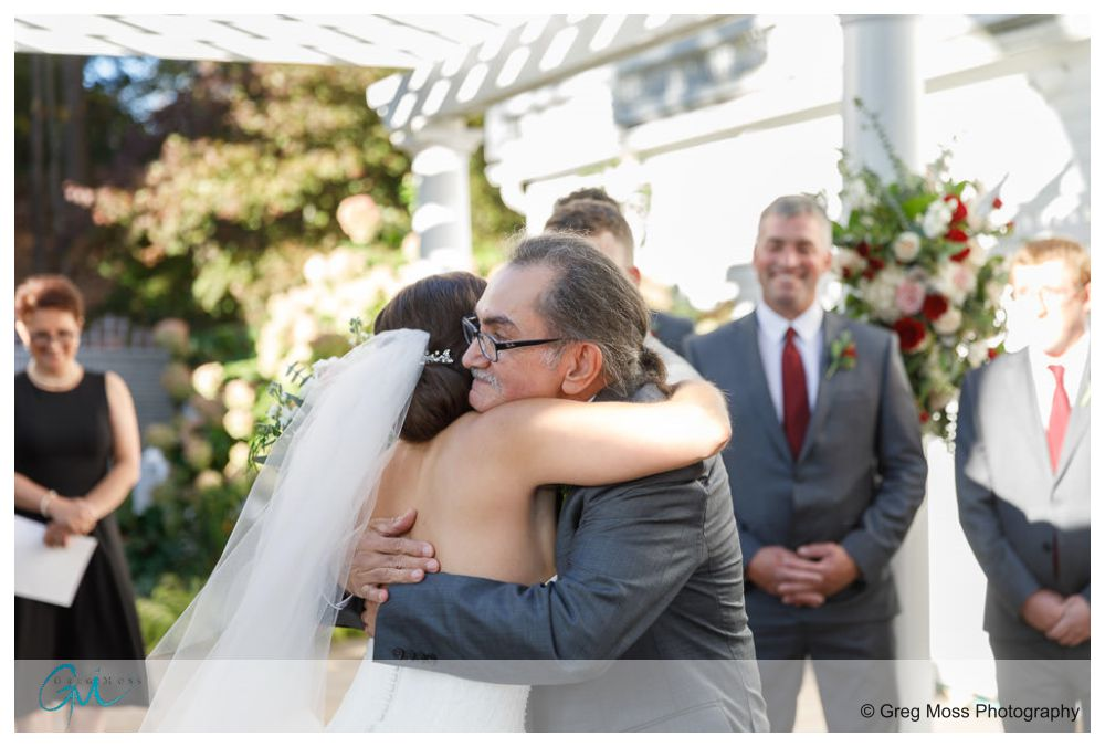 Father of the bride and Bride hugging at Alter
