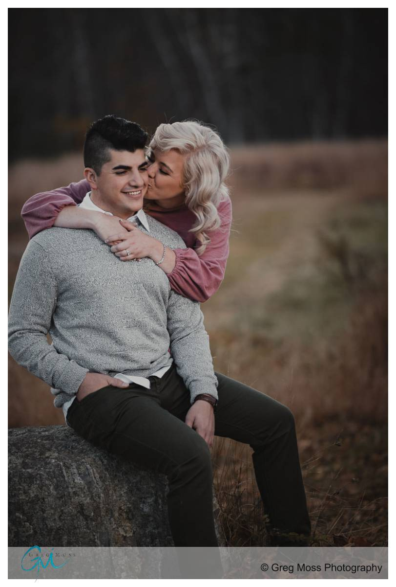 Girl kissing guy while hugging him from behind.