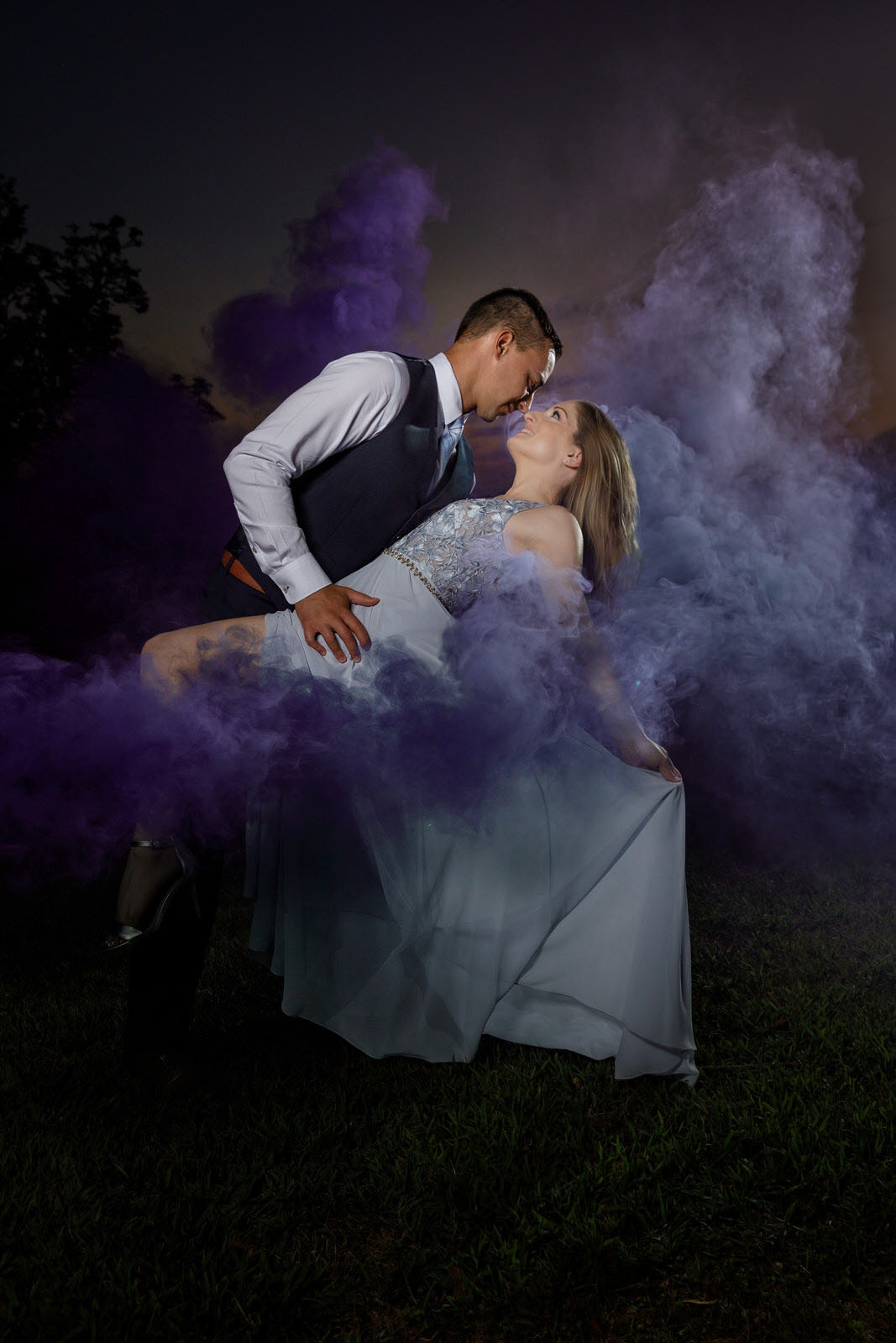 Elegantly dressed couple dipping at sunset with purple smoke