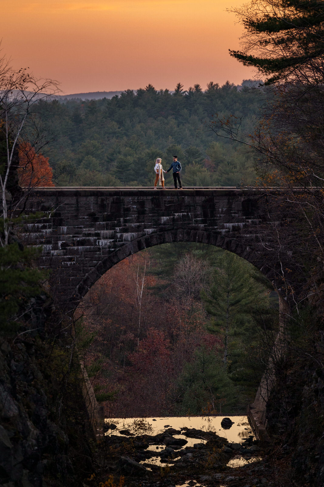 incredible engagement photo on spillway bridge at Quabbin Reservoir