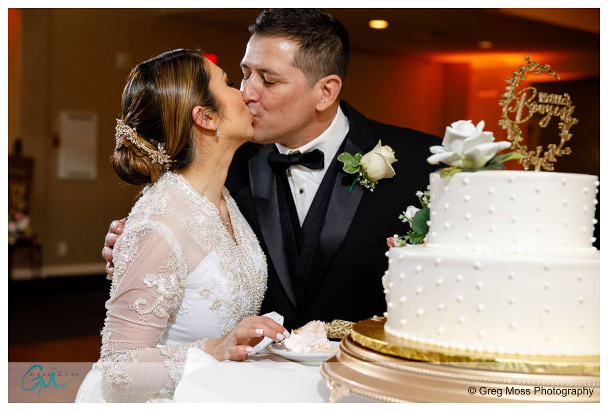 Bride and groom cake cutting in the ballroom at the Delaney House