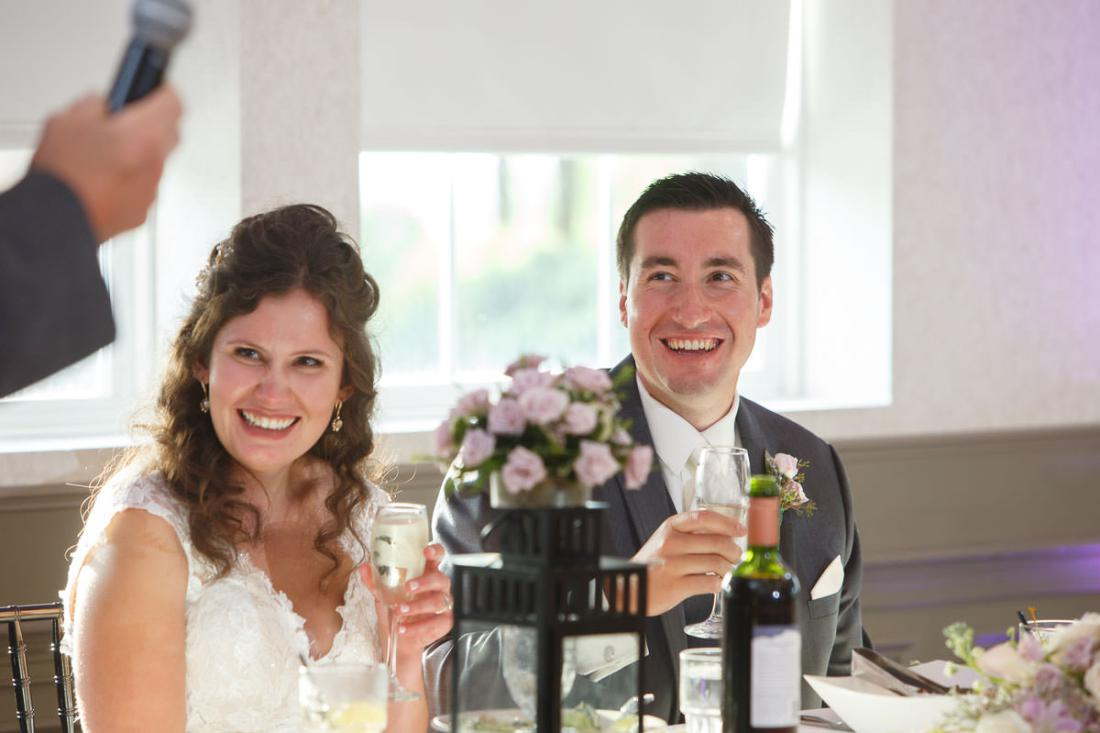 Bride and groom laughing during father of the bride speech