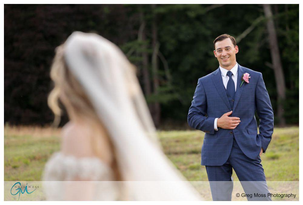 Groom smiling at bride in field