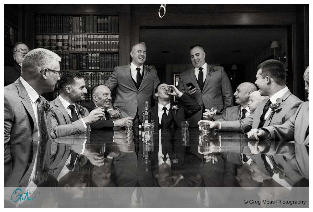 Black and White photo of Groom, Fathers, groomsmen in library at publick house toasting with whiskey