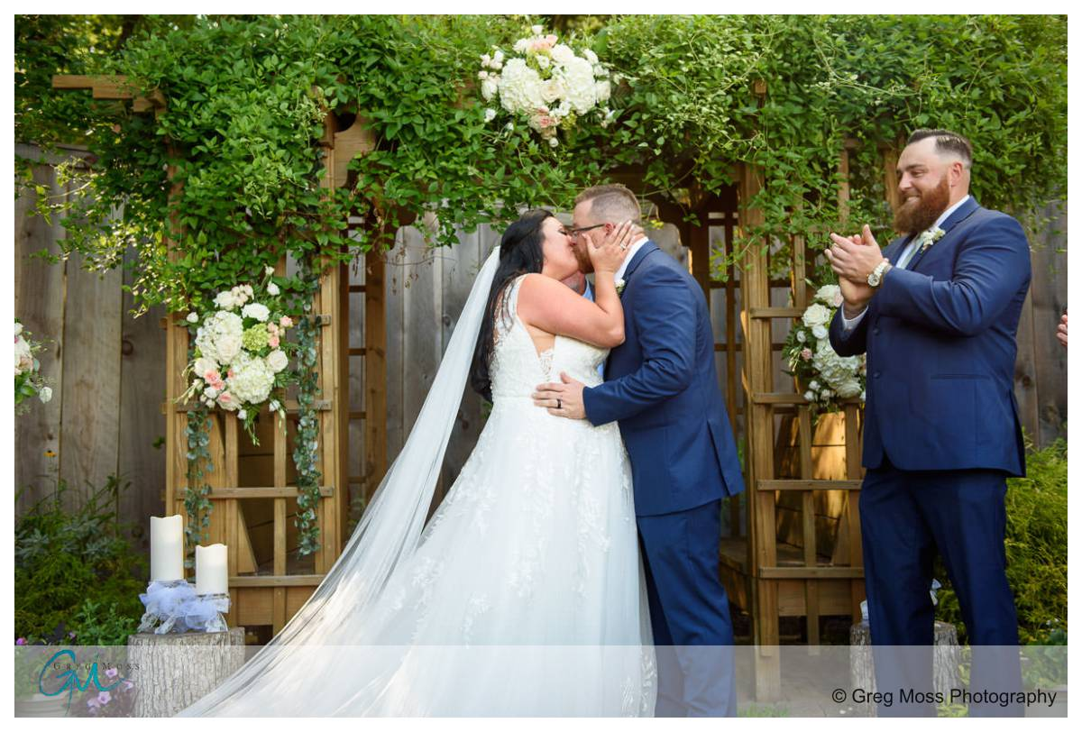 Bride and groom first kiss outside ceremony
