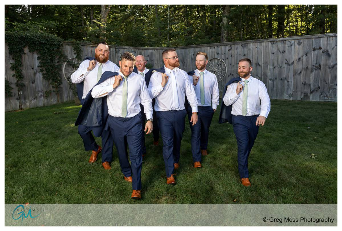 Walking photo of groom and groomsmen with jackets over their shoulders