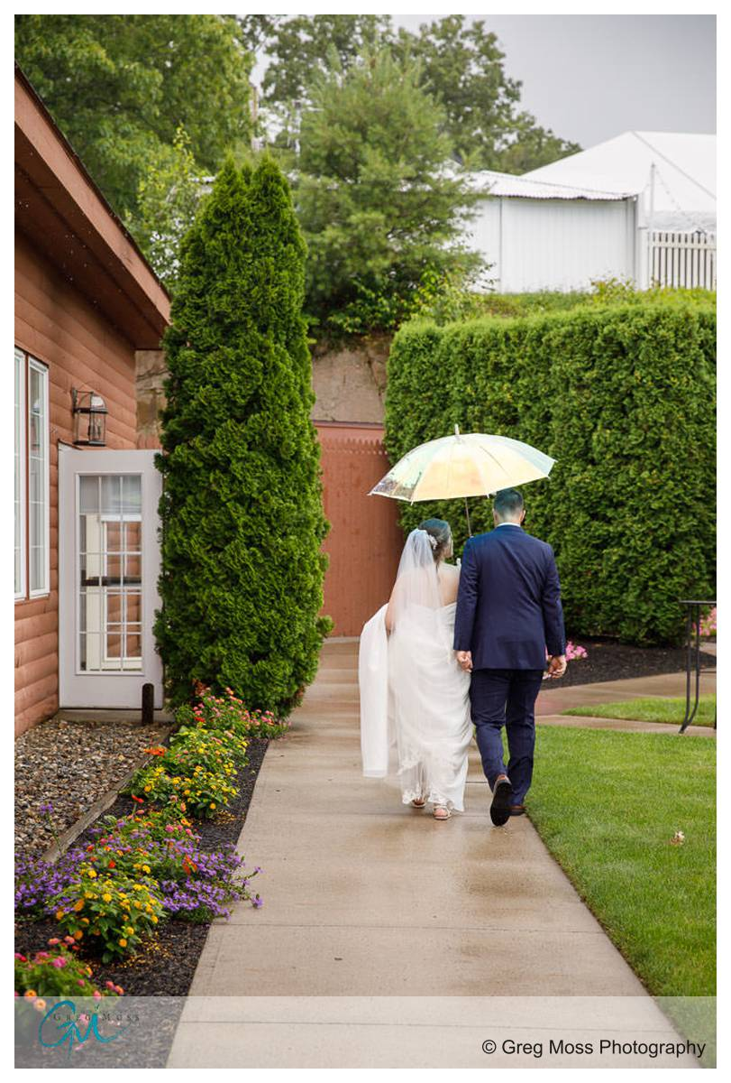 Bride and groom walking with clear umbrella after first look