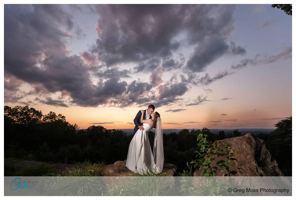 Stunning Dramatic sunset photo of wedding couple at the Log Cabin