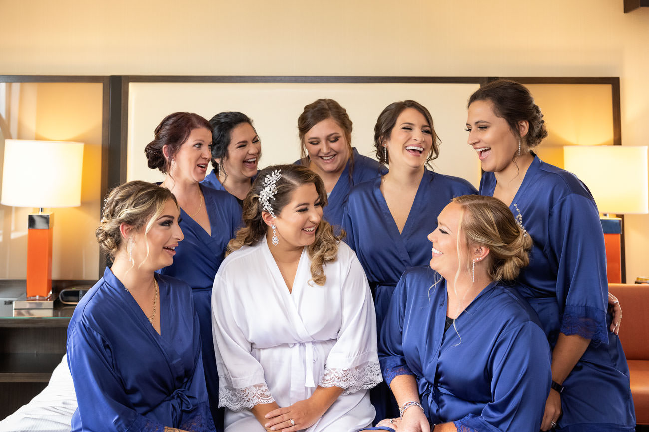 Bride and bridesmaids hugging on bed with matching monogramed robes