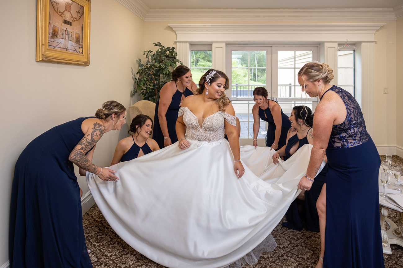 Bridesmaids fanning brides dress.