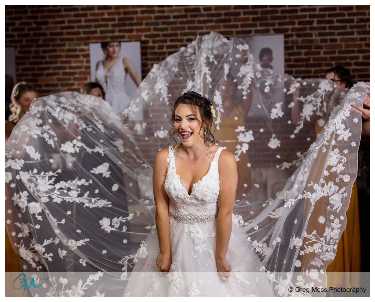 Bride and bridesmaids with bridesmaids fanning dress