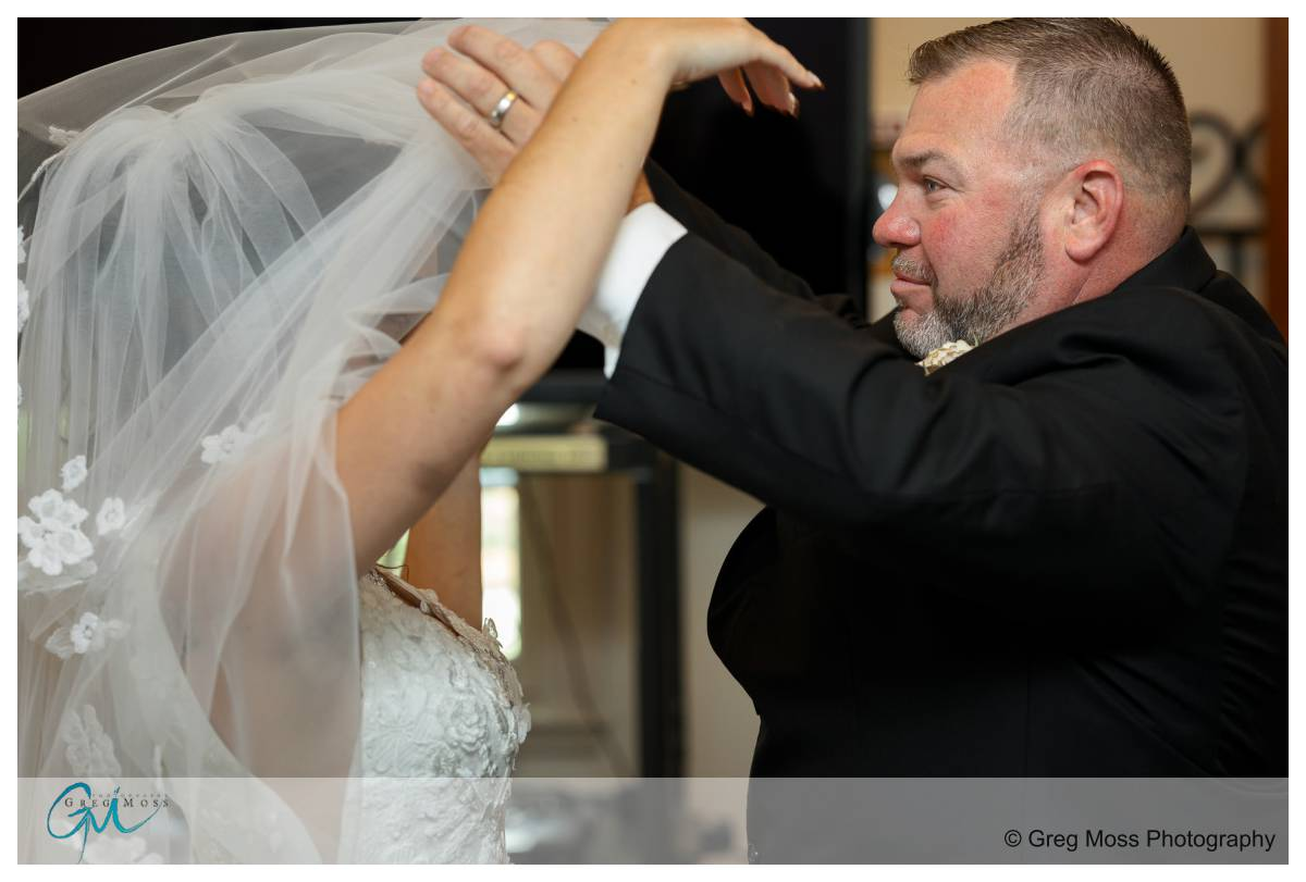 Dad pulling veil over bride before she walks down the aisle.