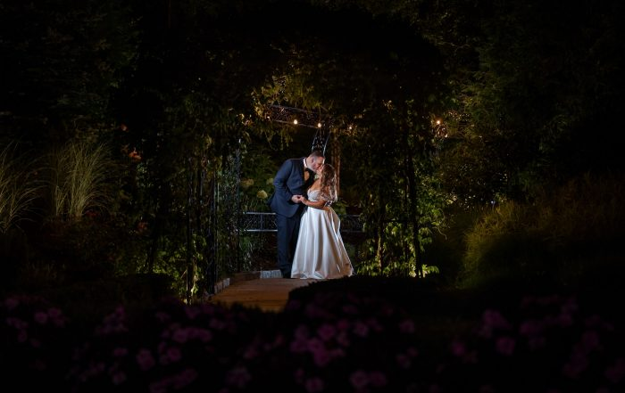 wedding couple under twinkle lights and ivy at Aria Wedding