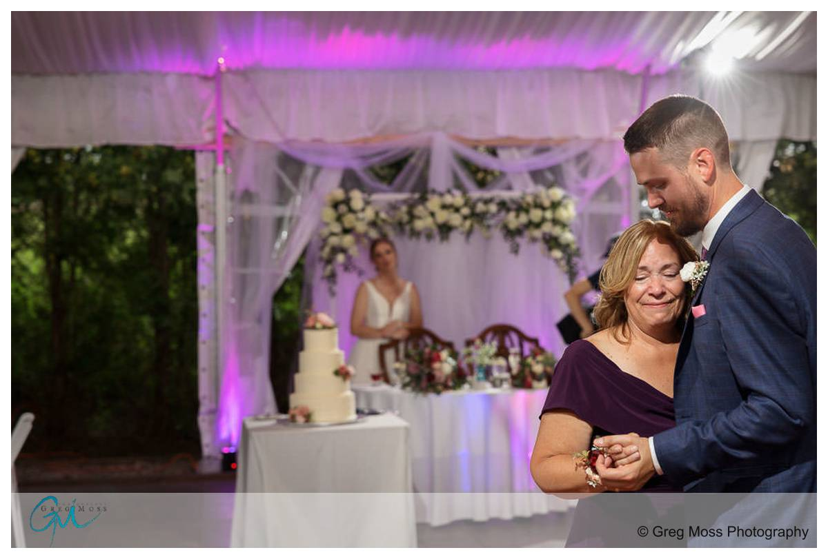 Mother son dance with bride watching