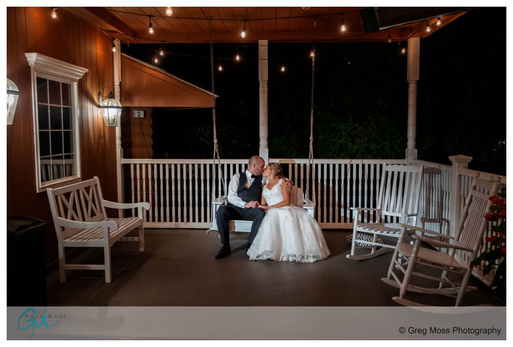 Wedding couple on bench swing in front of the Log Cabin Holyoke