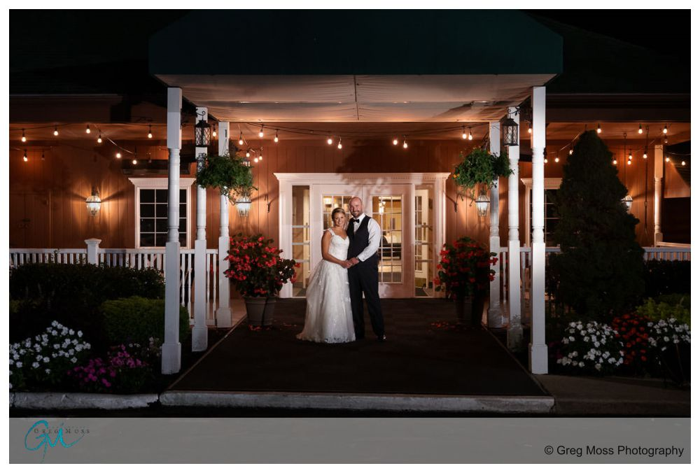 Bride and groom in front of the Log Cabin Holyoke at night